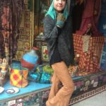 A PEOPLE UNITED knit poncho, $92, ANGIE tan micro-suede bell bottoms, $65, LITTLE JOURNEYS Peruvian wool teal and green hat, $48, and fingerless gloves, $49