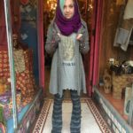 """Hooded sweater by A PEOPLE UNITED, $108. Cashmere purple scarf, $92. 3/4 sleeve """"Create"""" top by CHRISTY FISHER. ANGIE striped knit bell bottoms, $35."""