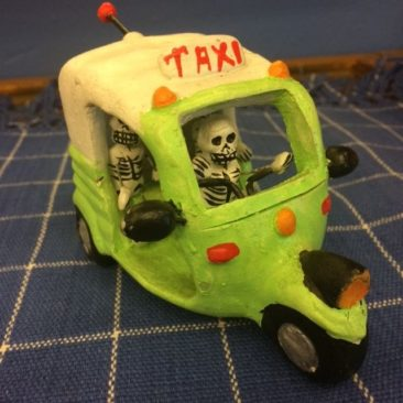 Day of the Dead figurines in taxi