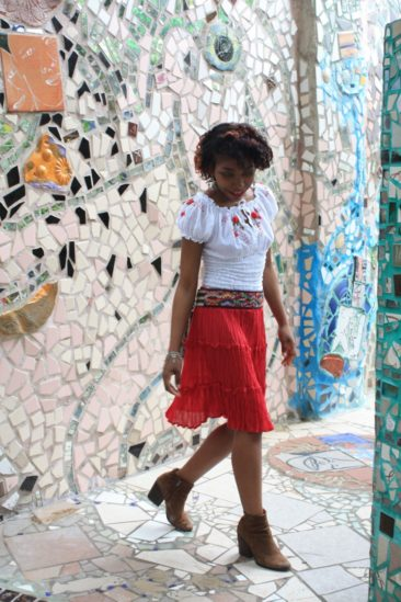 Jordan wears a  white blouse with rose embroidery, $36, with a red gauze Indian skirt, $17,  a vintage Guatemalan belt, $45, sterling bird earrings from Oaxaca, Mexico, $144, and a Matl vintage Mexican bracelet, $350.