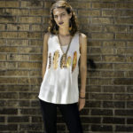 Orange feather tank top, $14.50; Black cropped pants with stitched ruffles by JEDZEBEL, $43; Brass and turquoise earrings by M. LIZ, $53; Brass and black beaded bracelet, $58