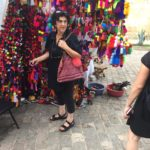 Julia perusing pom pom selections at a market in Oaxaca